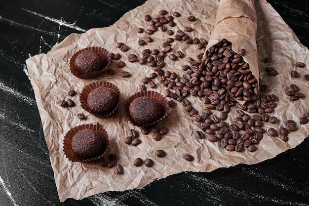 プラリネと黒の背景にコーヒー豆。 無料写真