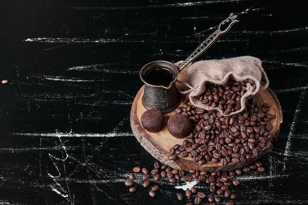 Кофейные зерна на черном фоне с пралине. Бесплатные Фотографии