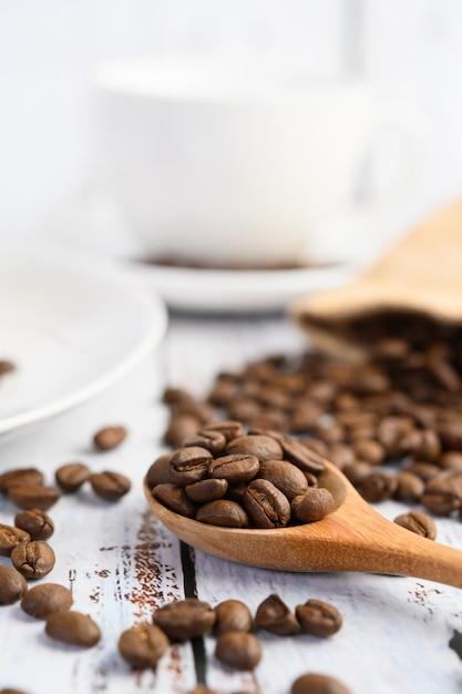 Кофейные зерна на деревянной ложке и пеньке кладут в мешки на белой деревянной таблице. Бесплатные Фотографии
