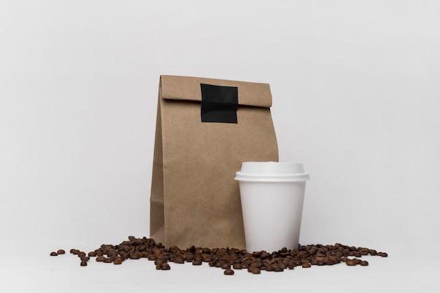 Disposizione dei chicchi di caffè e del sacchetto di carta Foto Gratuite