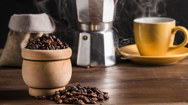 Chicchi di caffè in pentola vicino set di caffè, sacco e caffettiera Foto Gratuite