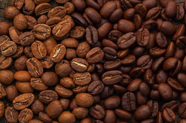 コーヒー豆のテクスチャ高品質の背景。焙煎したコーヒー豆。さまざまな種類の焙煎コーヒー豆の背景の混合物。 Premium写真