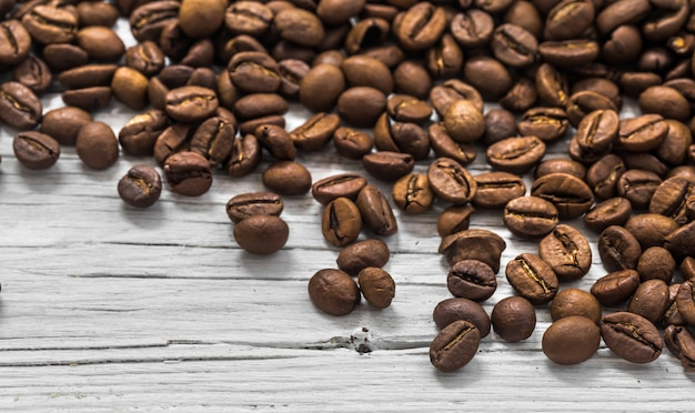 Coffee beans on white wooden background, closeup Free Photo
