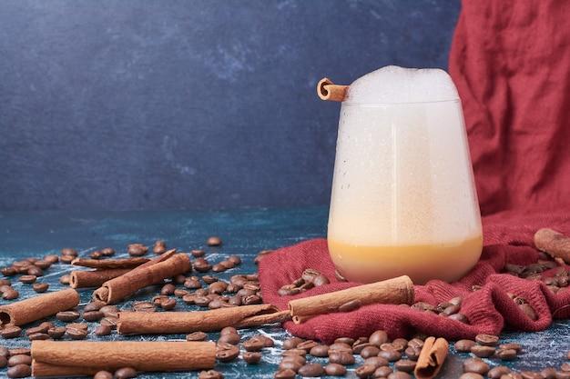 Кофейные зерна с чашкой напитка на синем. Бесплатные Фотографии