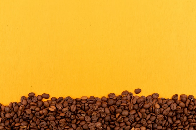 Coffee beans with copy space on yellow surface Free Photo