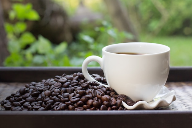 Coffee beans with white coffee mug blur background, a cup of hot coffee is placed beside the coffee beans Premium Photo