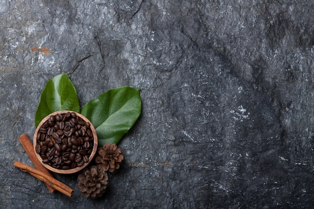 Coffee beans in wood cup on green leaf ,  pine on black stone Premium Photo