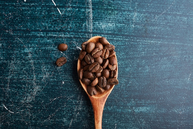 Coffee beans in a wooden spoon. Free Photo