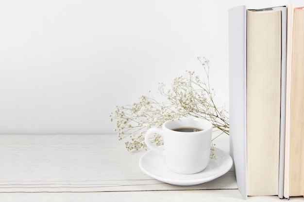 Coffee next to books with copy space Free Photo