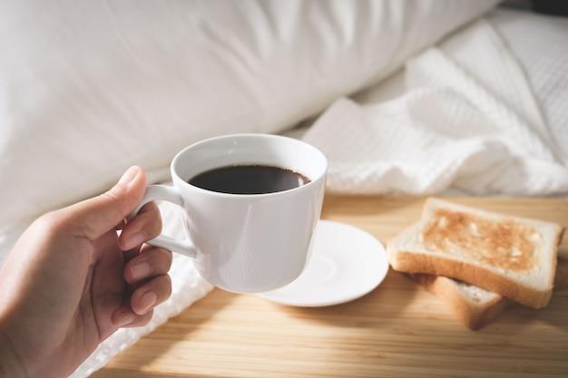 トーストしたパンが付いているベッドに置かれた白いカップのコーヒーパン Premium写真