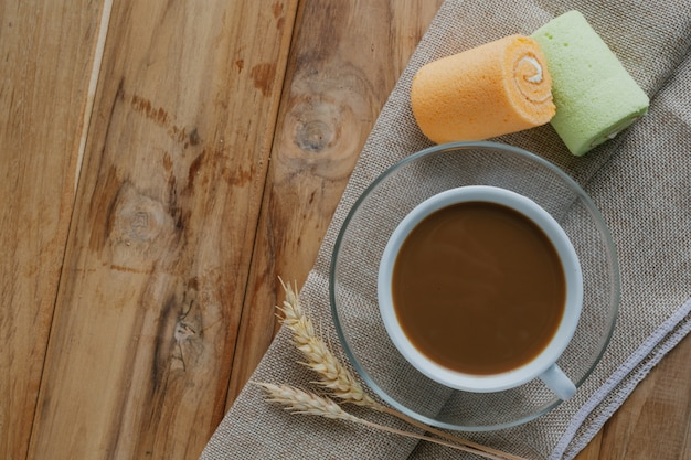 Coffee and bread placed on brown wood floors. Free Photo