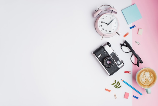 Coffee cup; alarm clock; retro camera; eyeglasses and retro camera on white and pink dual backdrop Free Photo