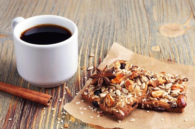 コーヒーカップと古い木製のテーブル上のナッツクッキー Premium写真