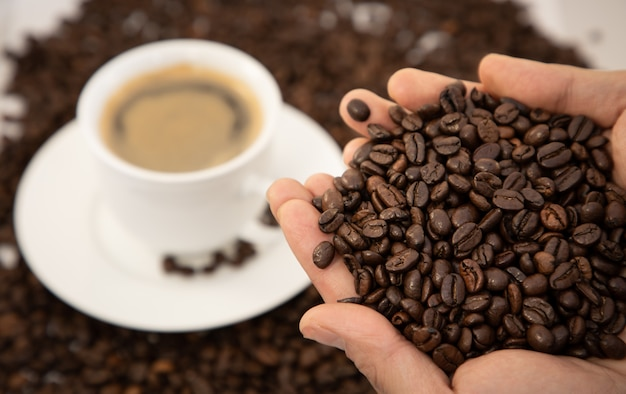 Coffee cup and beans close-up on wooden table background. Premium Photo