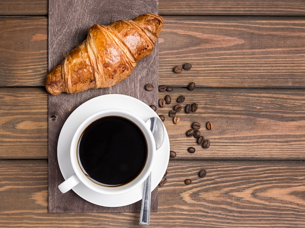 Coffee cup, beans and croissant on wooden background on the table Premium Photo