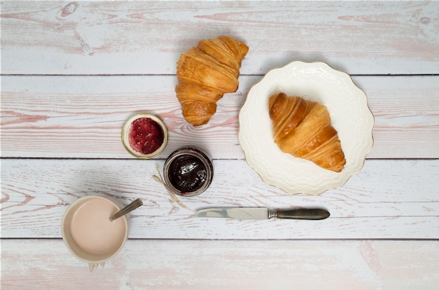 Coffee cup; berry jam and croissant with knife on wooden desk Free Photo