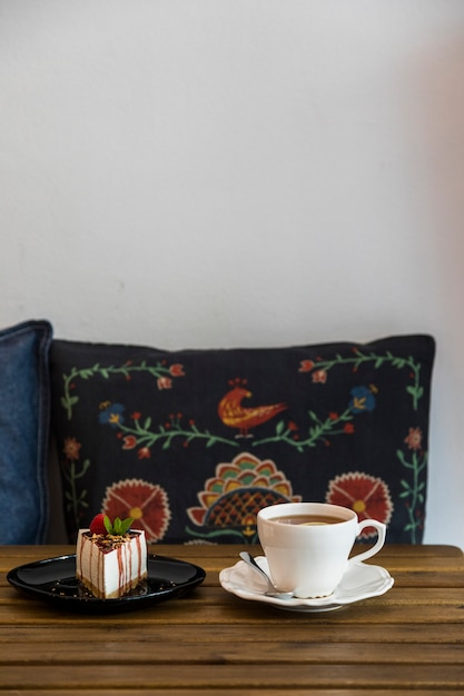 Coffee cup and cheesecake on wooden table in front of cushion against the white wall Free Photo