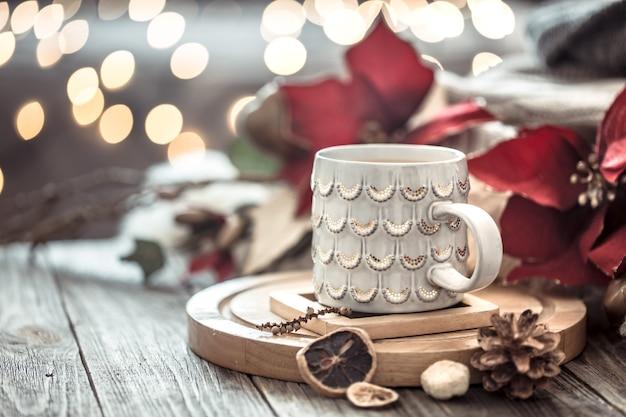 Tazza di caffè sopra il bokeh delle luci di natale in casa sulla tavola di legno con i fiori su una parete e sulle decorazioni. decorazione natalizia, magico natale Foto Gratuite