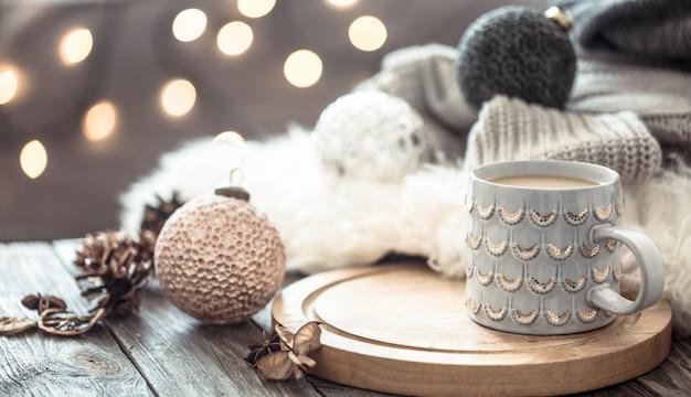 Tazza di caffè sopra bokeh di luci di natale in casa sul tavolo di legno con maglione su una parete e decorazioni. decorazione natalizia, magico natale Foto Gratuite