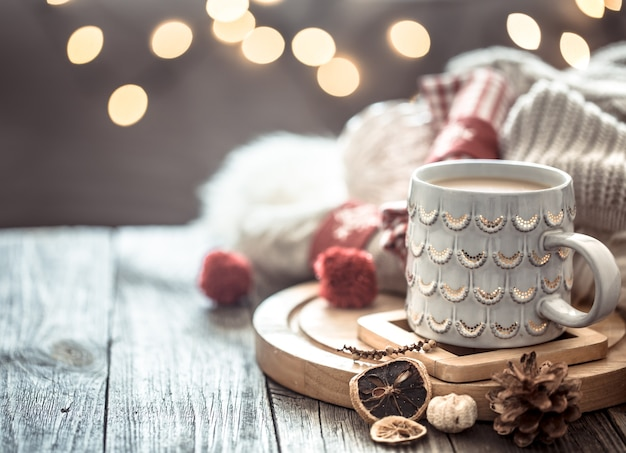 Coffee cup over christmas lights bokeh in home on wooden table with sweater on a wall and decorations. holiday decoration, magic christmas Free Photo