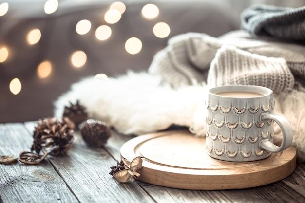 Tazza di caffè sopra bokeh di luci di natale in casa sul tavolo di legno con maglione su una parete e decorazioni. decorazione per le vacanze Foto Gratuite