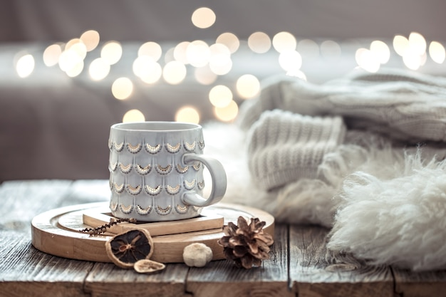Coffee cup over christmas lights bokeh in home on wooden table with sweater on a wall and decorations. holiday decoration Free Photo
