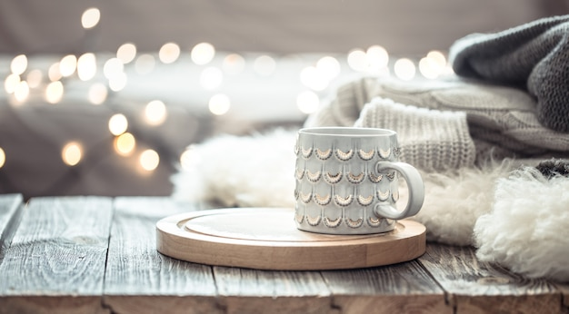 Coffee cup over christmas lights bokeh in home on wooden table with sweater on a wall. holiday decoration, magic christmas Free Photo
