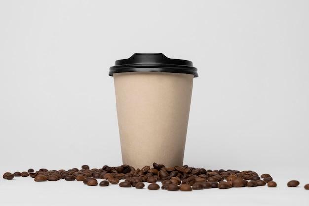 Tazza di caffè sulla disposizione dei chicchi di caffè Foto Gratuite