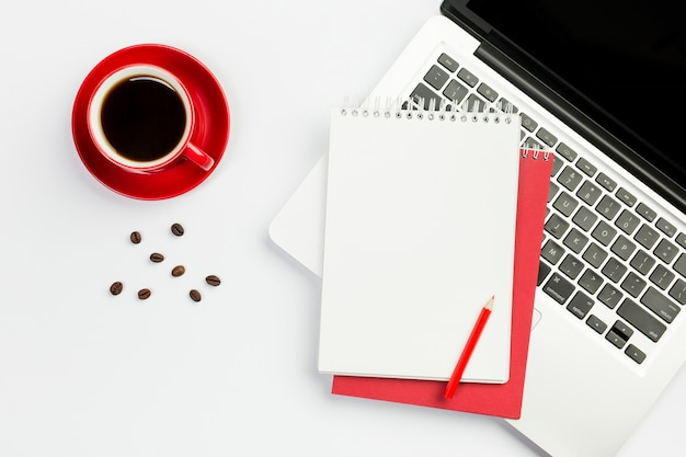 Coffee cup,coffee beans with spiral notepad on an open laptop against white background Free Photo