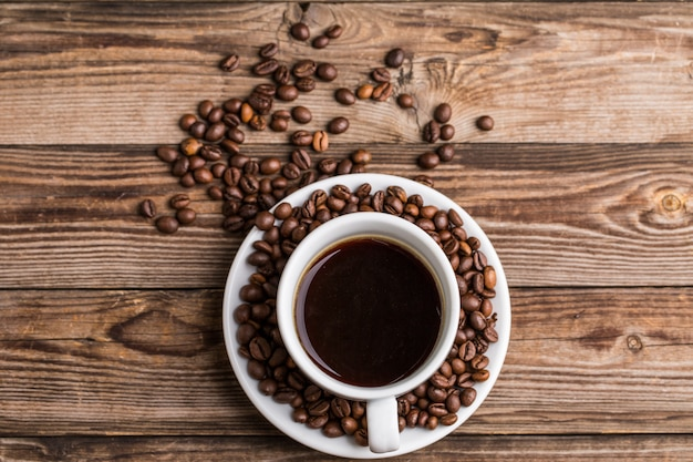 Coffee cup and coffee beans on wooden background. Premium Photo