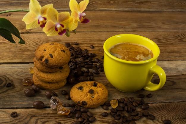 コーヒーカップ、クッキー、黄色の蘭 Premium写真