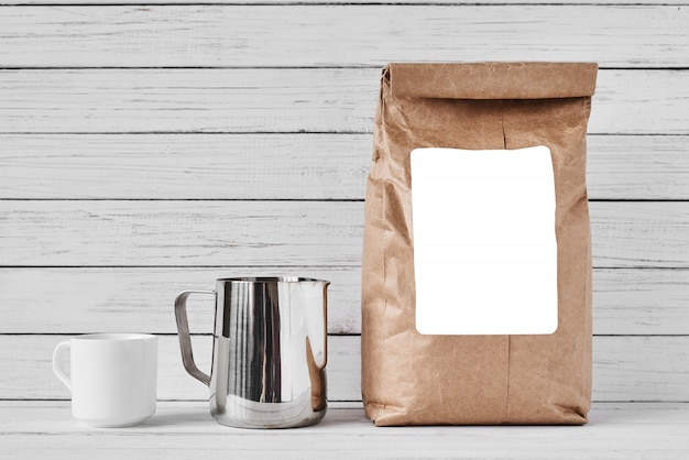Coffee cup, craft paper bag and stainless pitcher Premium Photo