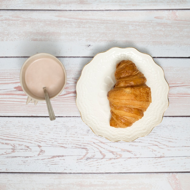 Coffee cup and croissant on ceramic plate over wooden table Free Photo