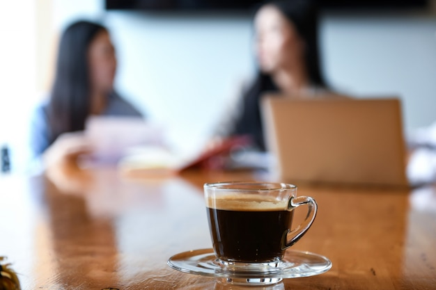 Coffee cup on deak in the meeting room. blurred background workers are sitting. Premium Photo