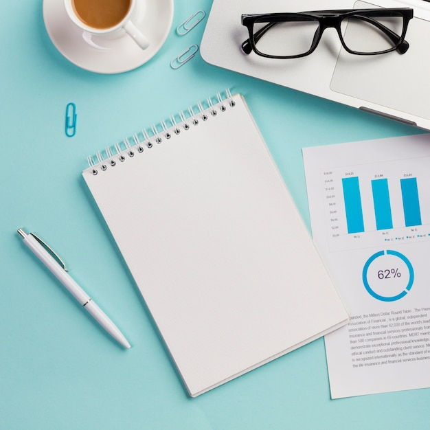 Coffee cup,eyeglasses,laptop,eyeglasses,data paper,pen and blank spiral notepad Free Photo