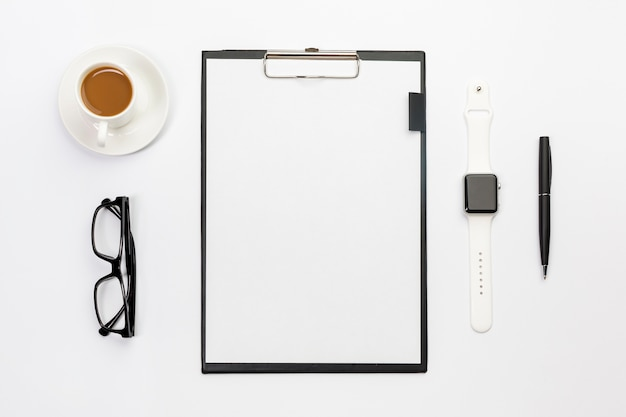 Coffee cup,eyeglasses,smart watch,pen and blank paper clipboard on white desk Free Photo