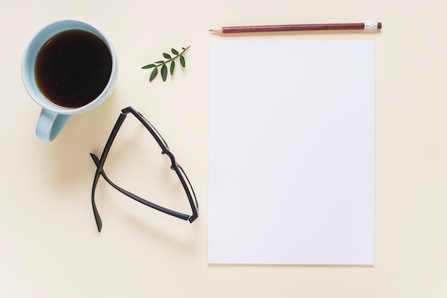 Coffee cup; eyeglasses; twig; pencil and blank white page on beige backdrop Free Photo