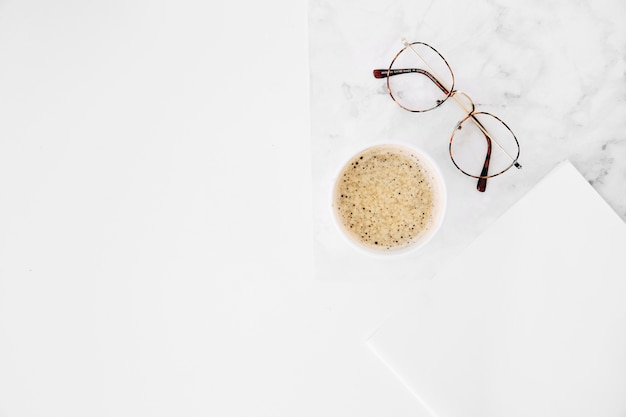 Coffee cup and eyeglasses with white paper on white background Free Photo