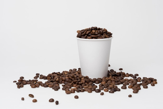 Coffee cup filled with coffee beans Free Photo