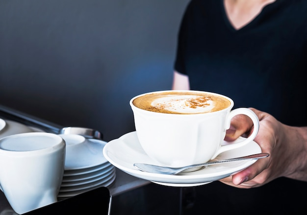 Coffee cup is serving by barista in the partial dark room shop Free Photo