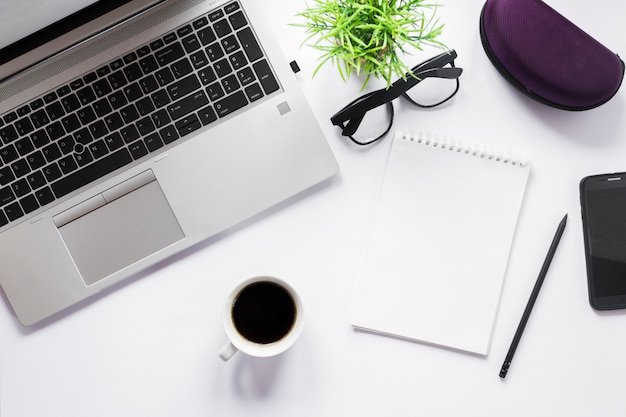 Coffee cup; laptop; eyeglasses; pencil and spiral notepad with pencil on white backdrop Free Photo