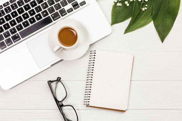 Coffee cup on laptop,eyeglasses,spiral notepad and leaves on white desk Free Photo