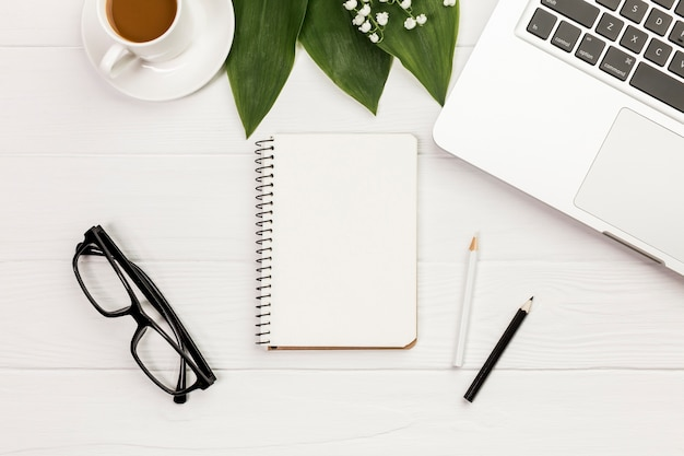 Coffee cup,leaves,spiral notepad,eyeglasses on office wooden desk Free Photo