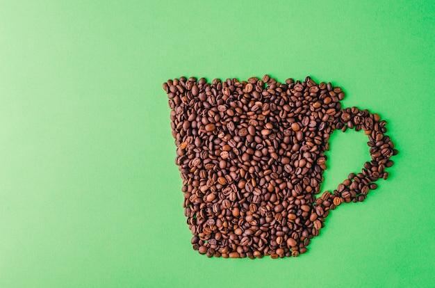 緑の背景にコーヒー豆で作られたコーヒーカップ-クールな壁紙に最適 無料写真