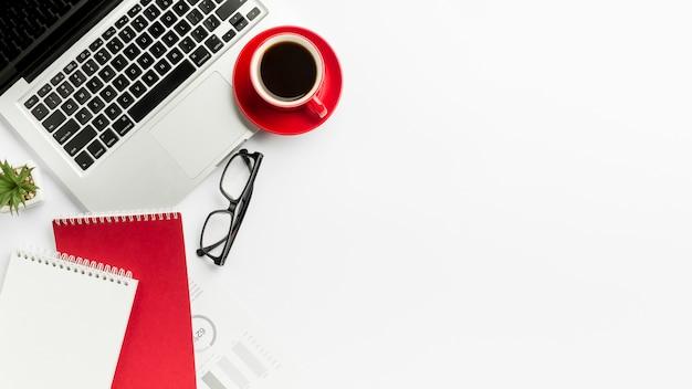 眼鏡と白い背景の上のスパイラルメモ帳のラップトップ上のコーヒーカップ Premium写真