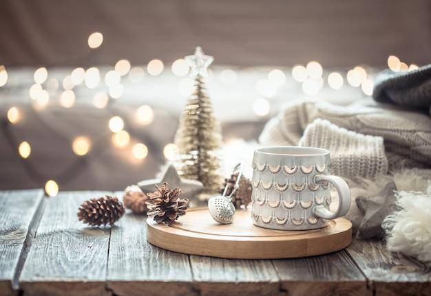크리스마스에 커피 컵 조명 Bokeh 벽 및 장식에 스웨터와 나무 테이블에 가정에서. 휴일 훈장, 마술 크리스마스 무료 사진