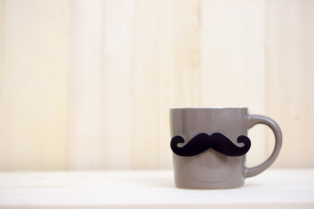 Coffee cup, paper mustache on wooden background with copy space. happy father's day. Premium Photo