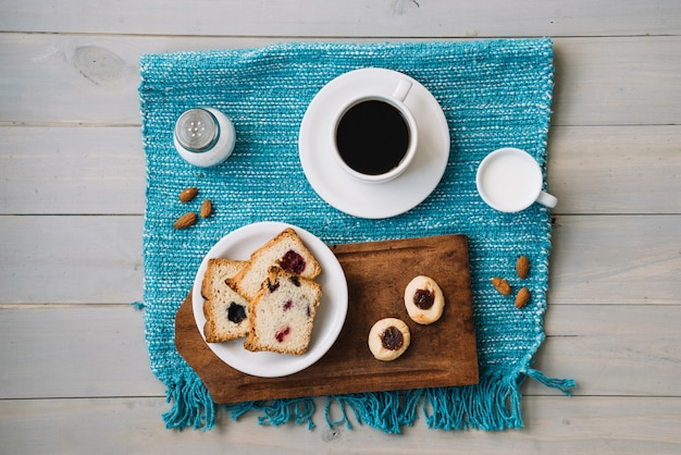 Coffee cup and pie with jam on table Free Photo