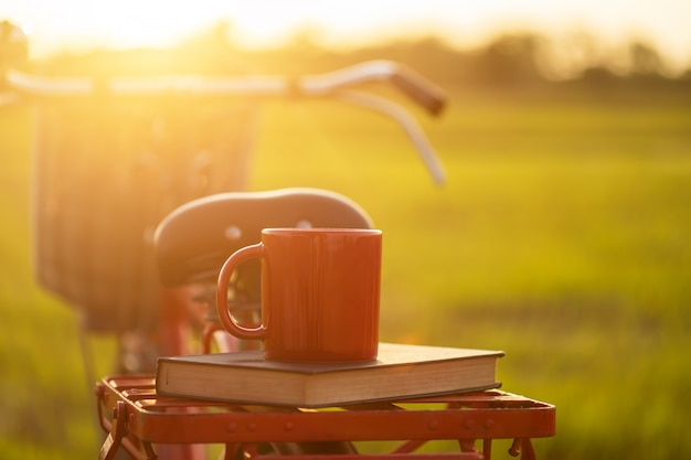 Coffee cup put on the red japan style classic bicycle at view of green rice field Premium Photo