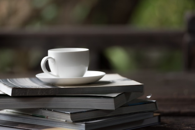 Coffee cup put on the stack of books in the morning. Premium Photo